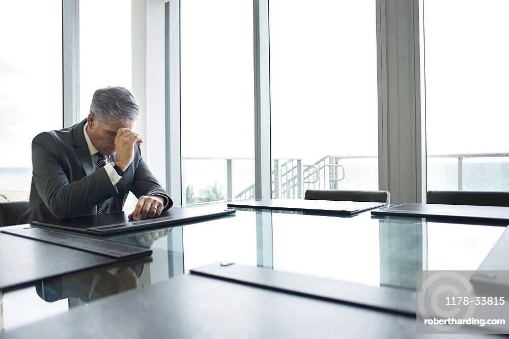 Caucasian businessman brooding at empty conference table