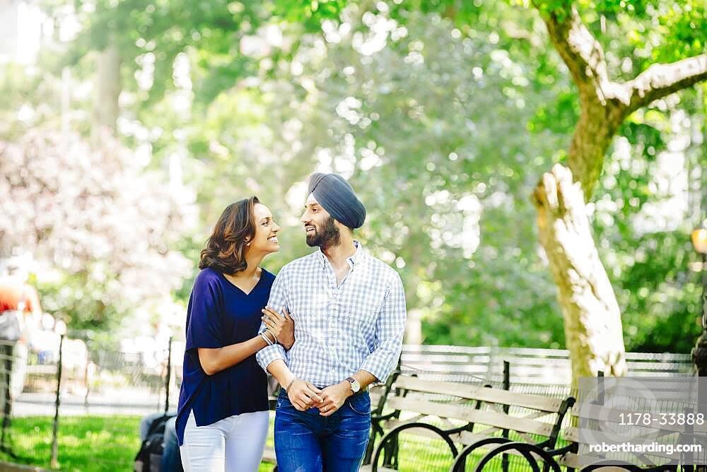 Indian couple walking in urban park