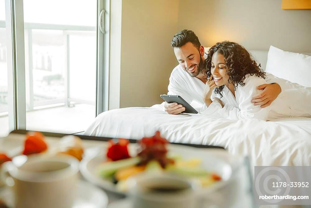 Couple using digital tablet on hotel bed