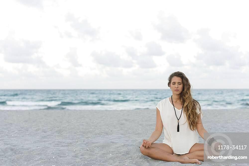 Hispanic woman meditating on beach