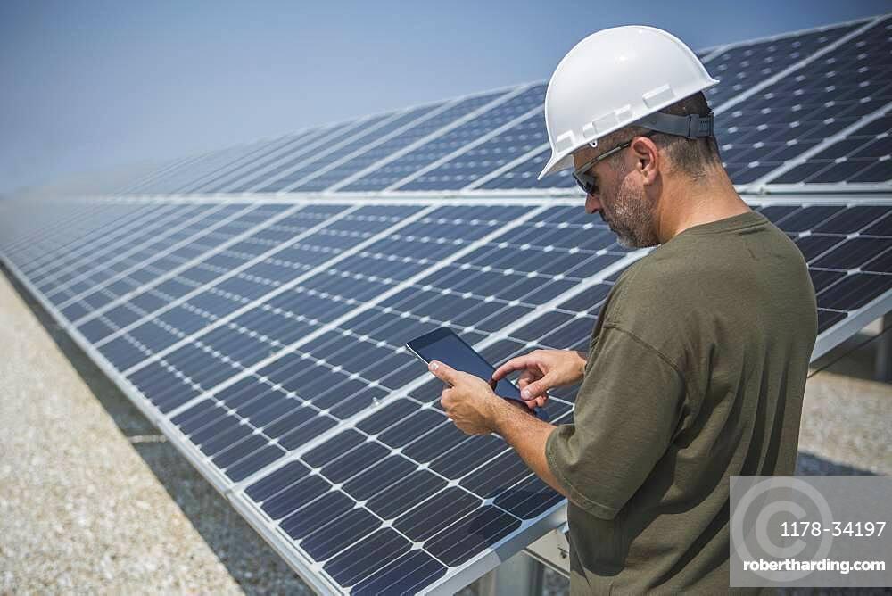 Caucasian technician using digital tablet near solar panels