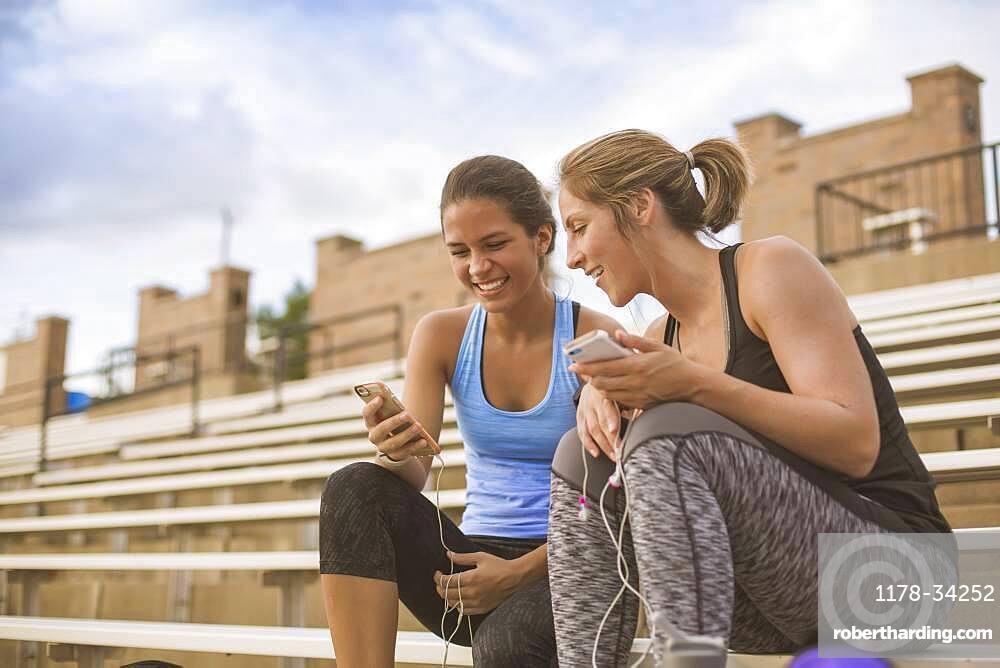 Women using cell phones on bleachers