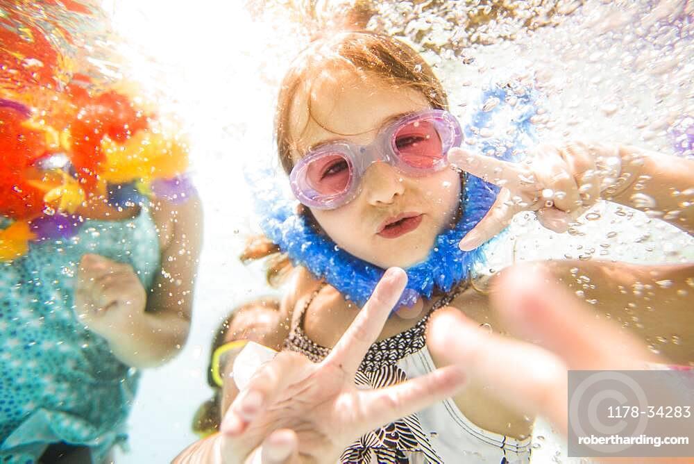 Caucasian children swimming underwater in swimming pool