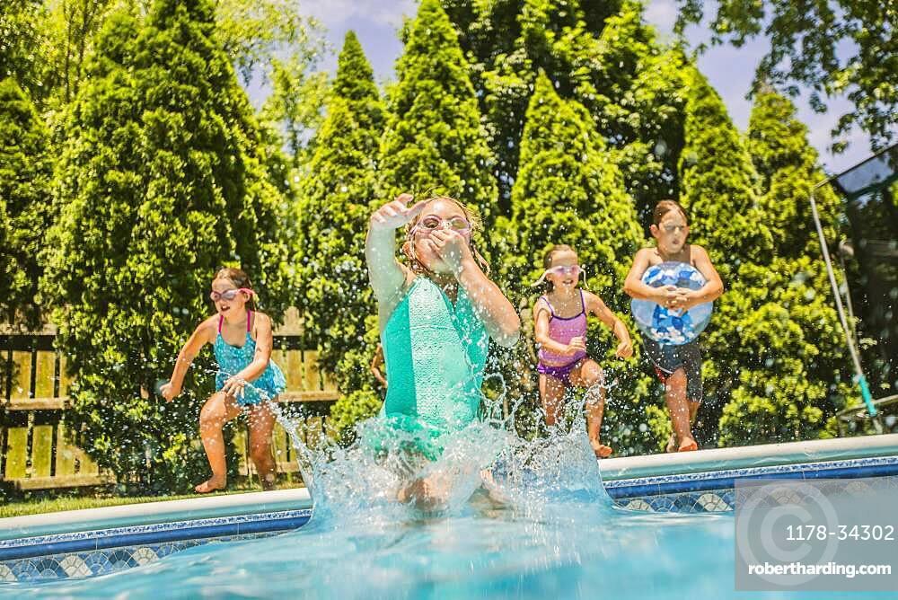 Caucasian girls jumping into swimming pool