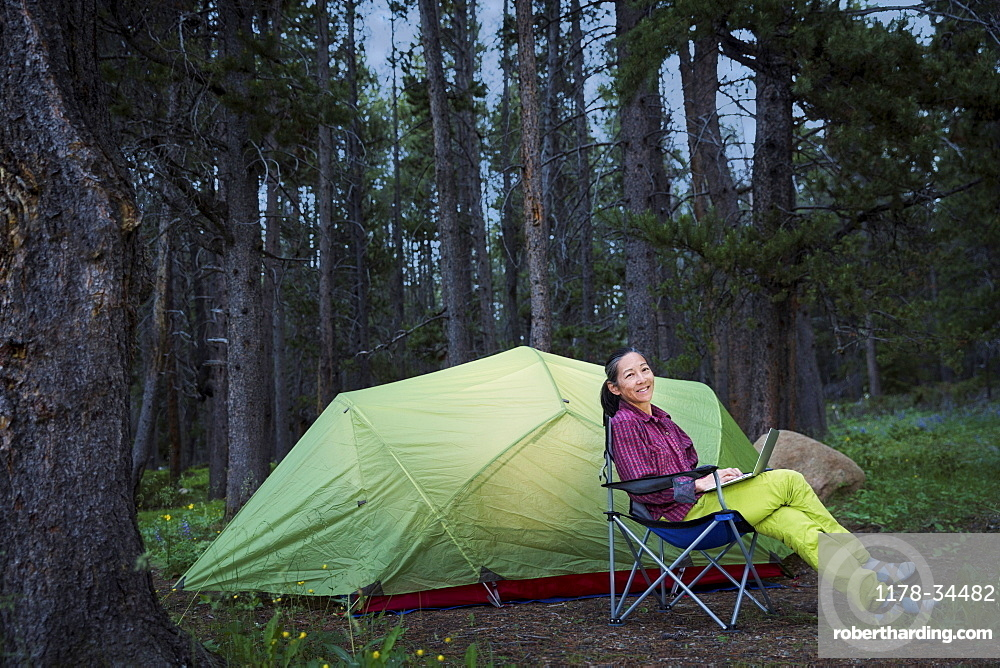 Japanese woman using laptop at campsite
