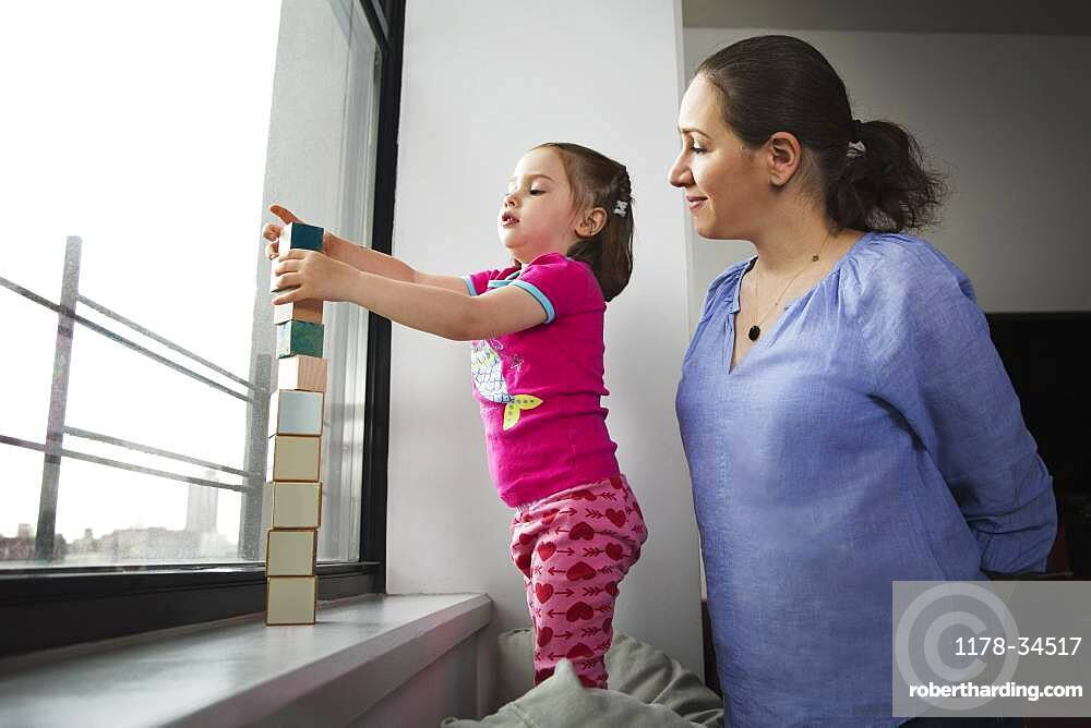 Mother and daughter stacking blocks in window