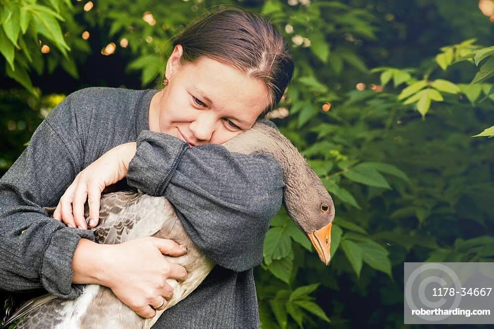Caucasian farmer hugging goose in garden