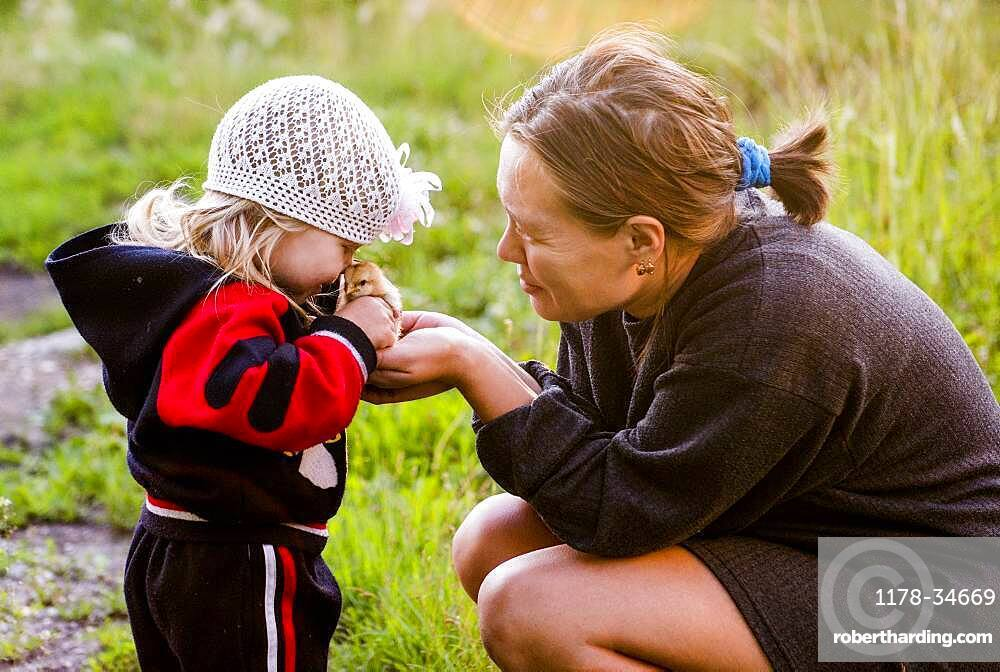 Caucasian mother and daughter playing with chick in garden
