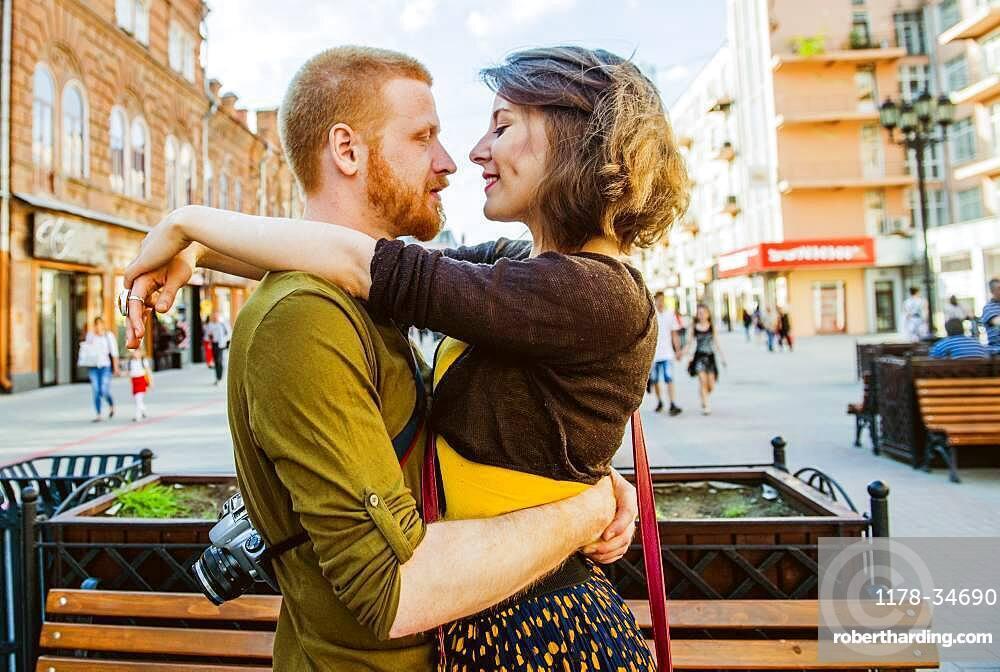 Caucasian couple hugging in city
