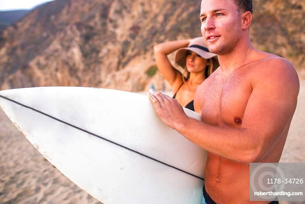 Caucasian surfer carrying surfboard on beach
