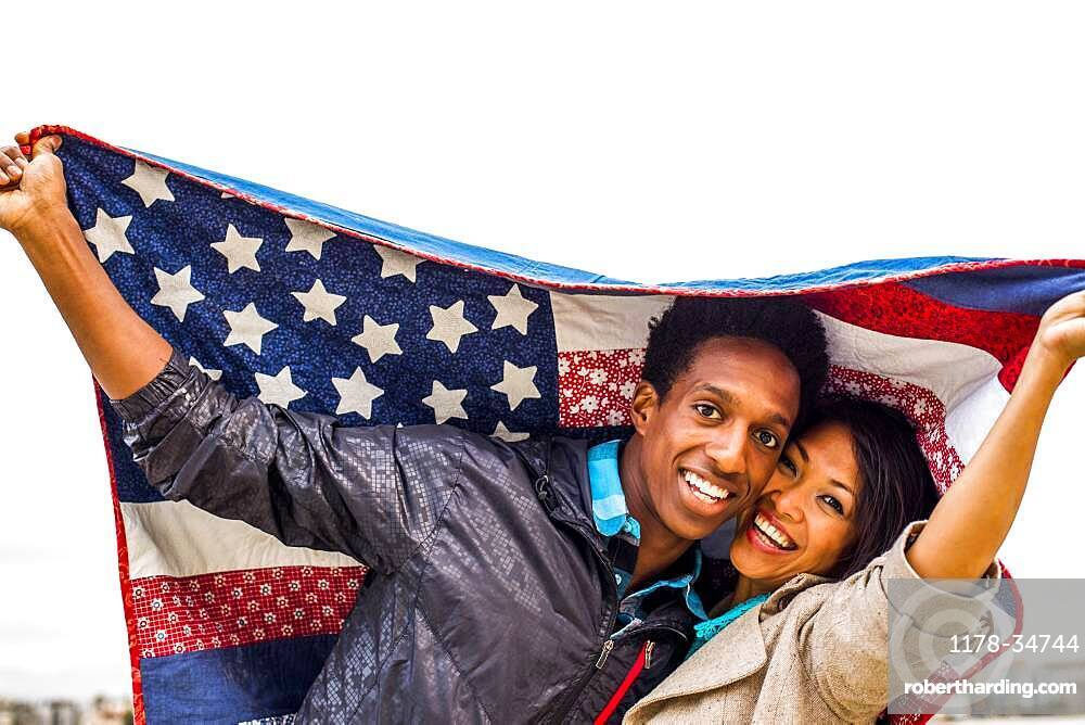 Couple holding American flag quilt outdoors