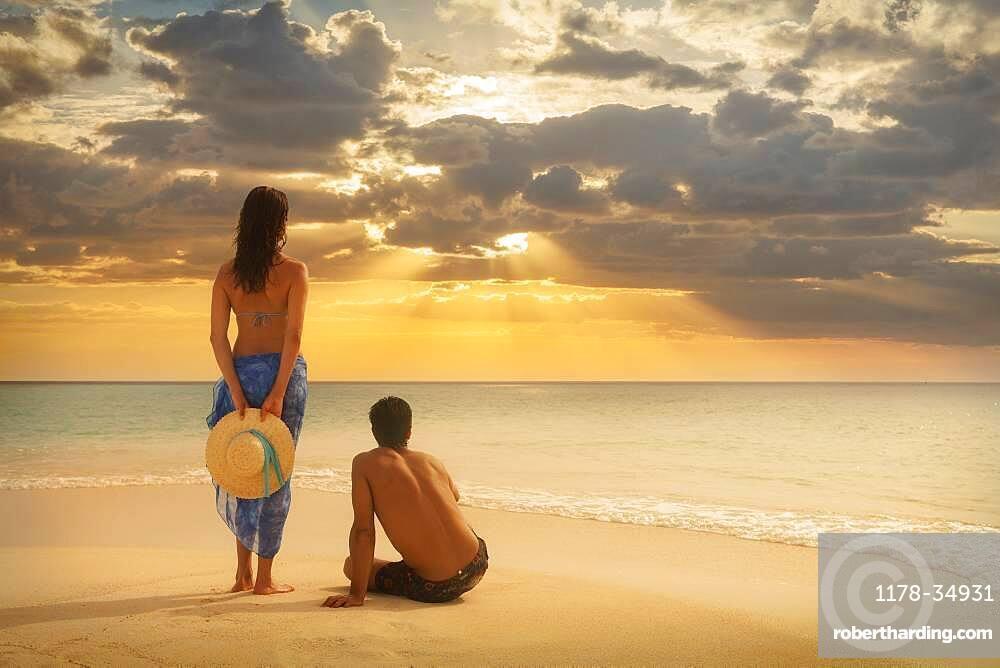 Caucasian couple admiring sunset on beach
