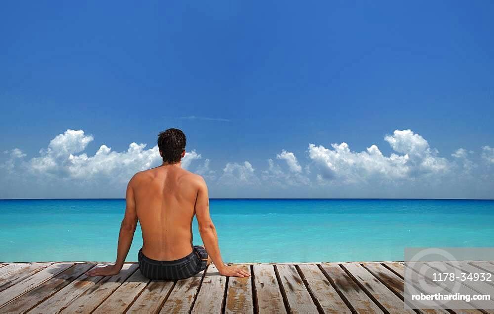 Caucasian man sitting on wooden dock at ocean