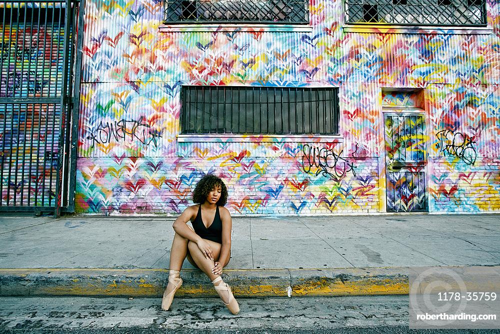 Mixed race ballet dancer sitting on curb rubbing leg