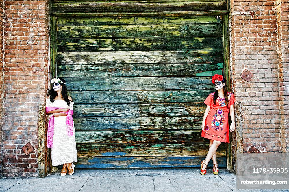 Women leaning on loading dock wearing skull face paint