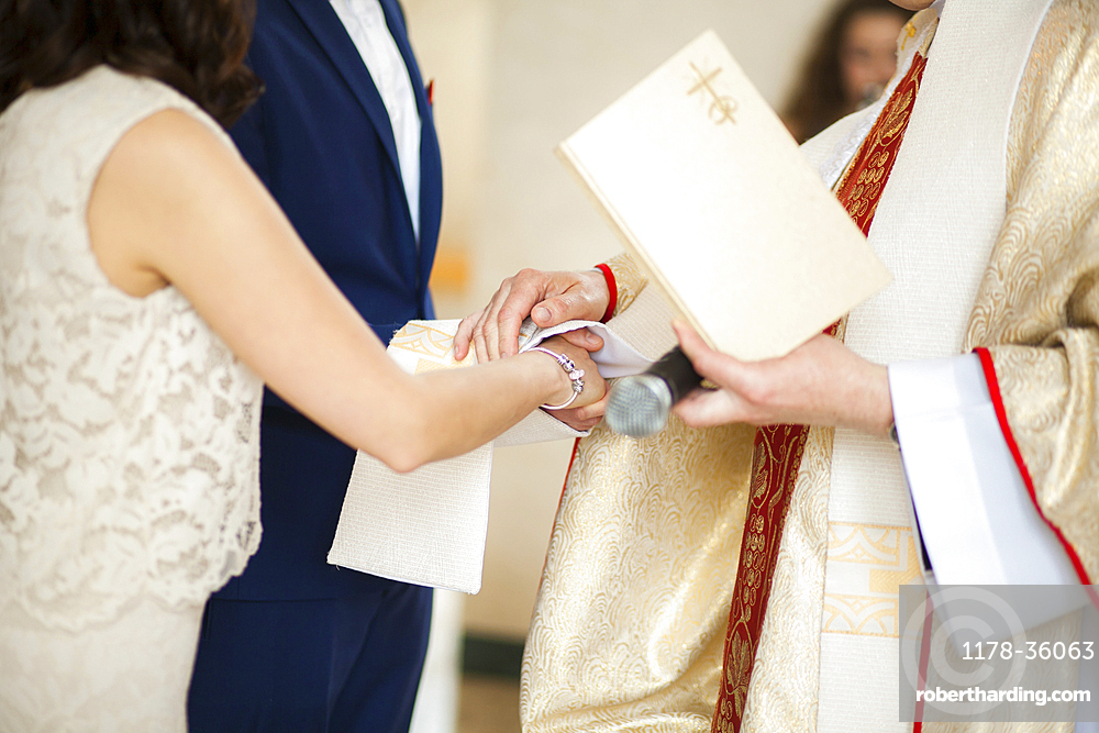 Priest and couple joining hands in wedding