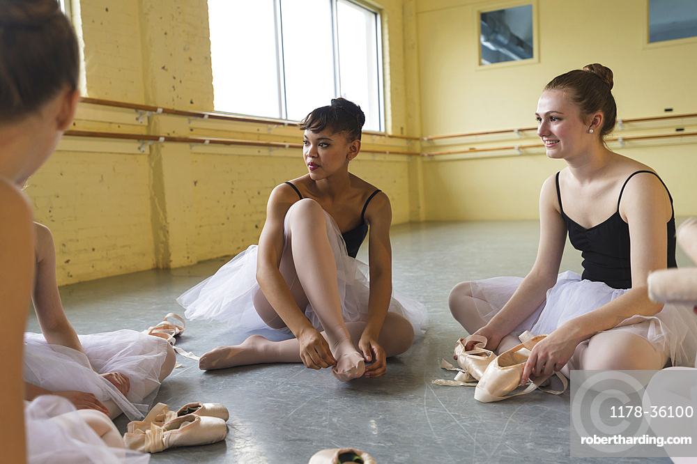 Girls sitting on floor and talking in ballet studio