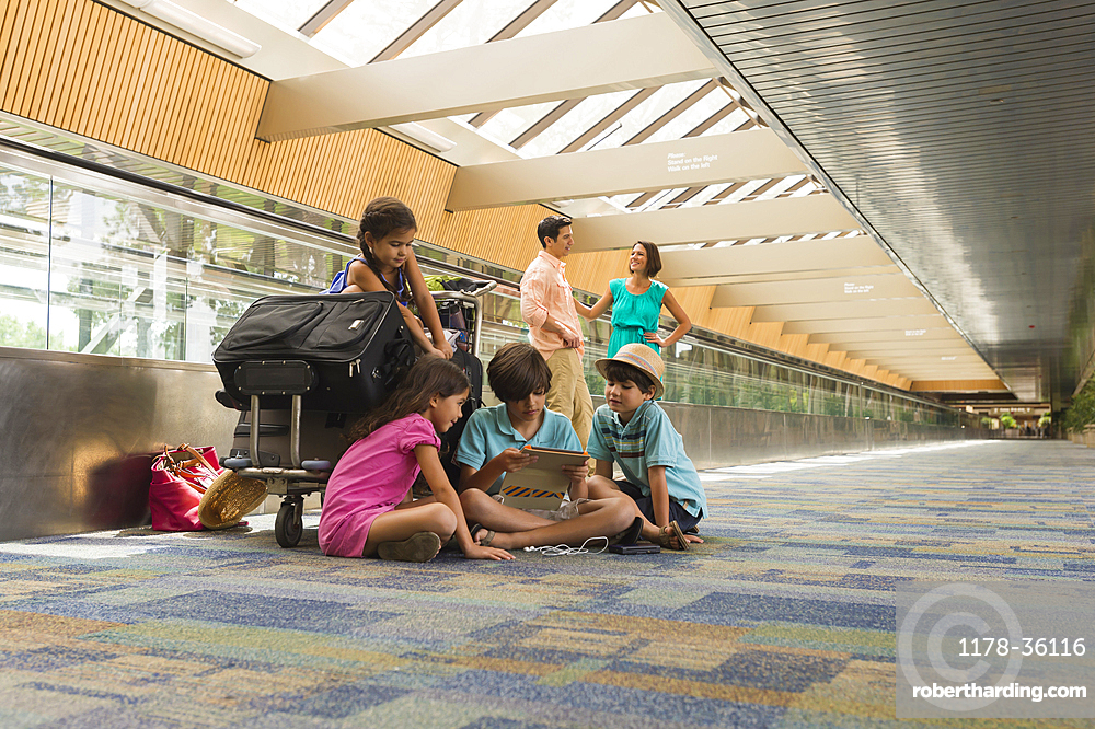 Children waiting in airport with family and using digital tablet