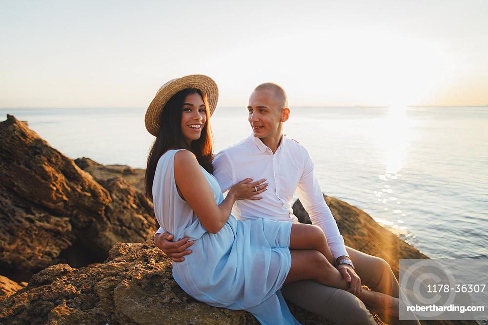 Caucasian couple sitting on rocks on beach at sunset