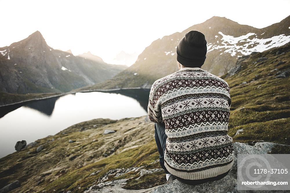 Caucasian man sitting on rock admiring scenic view of mountain lake