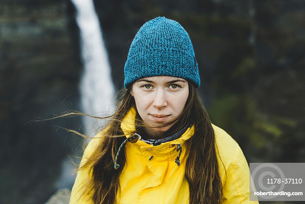 Wind blowing hair of Caucasian woman near waterfall