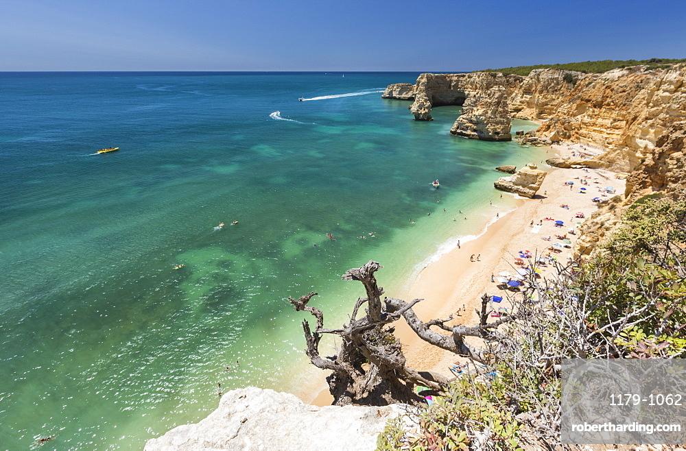 Tourists on sandy beach at Praia da Marinha surrounded by turquoise ocean, Caramujeira, Lagoa Municipality, Algarve, Portugal, Europe