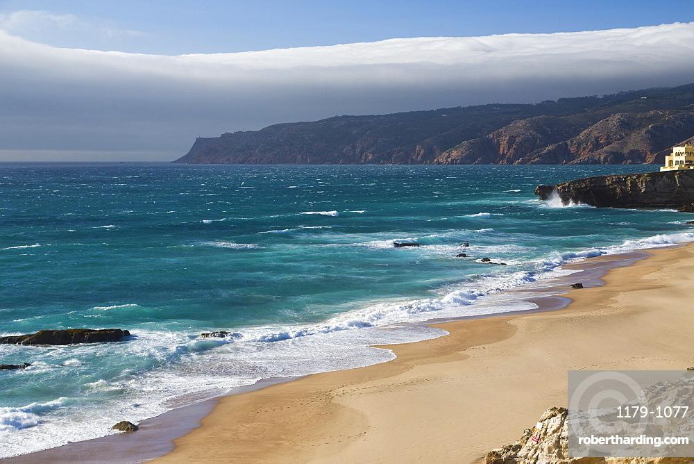 Ocean waves crashing on the sandy beach of Cascais, surrounded by cliffs, Estoril Coast, Lisbon, Portugal, Europe