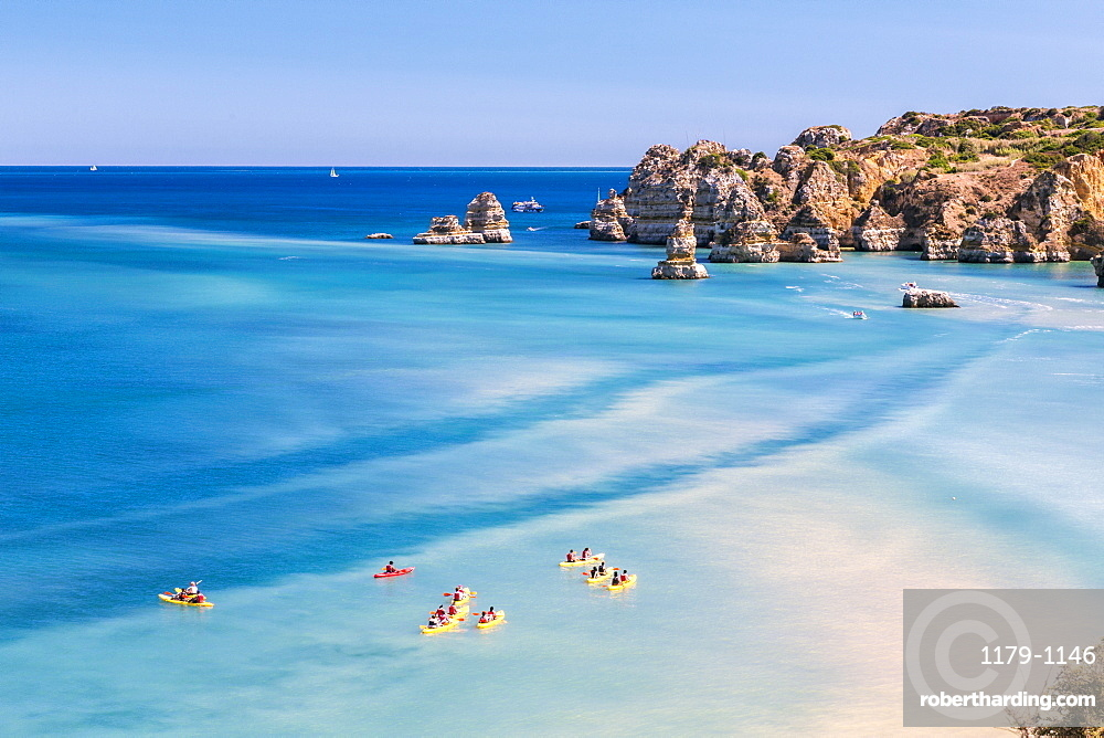 Canoes in the turquoise water of the Atlantic Ocean surrounding Praia Dona Ana beach, Lagos, Algarve, Portugal, Europe