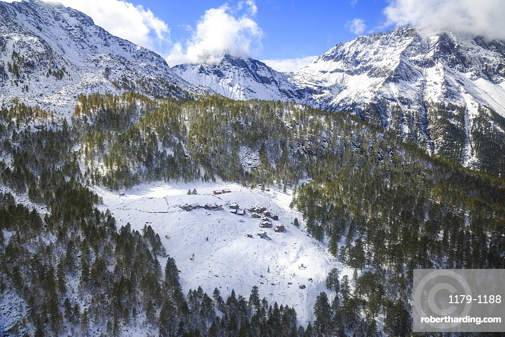 Aerial view of the alpine village of Laguzzola framed by woods and snowy peaks, Spluga Valley, Valtellina, Lombardy, Italy, Europe