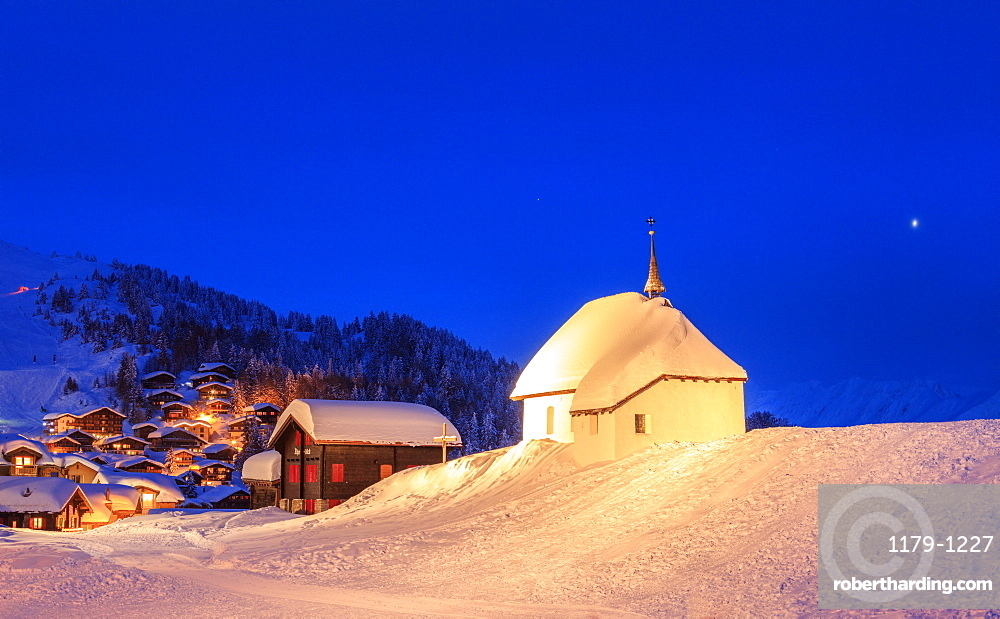 Blue dusk on the alpine village and church covered with snow, Bettmeralp, district of Raron, canton of Valais, Switzerland, Europe