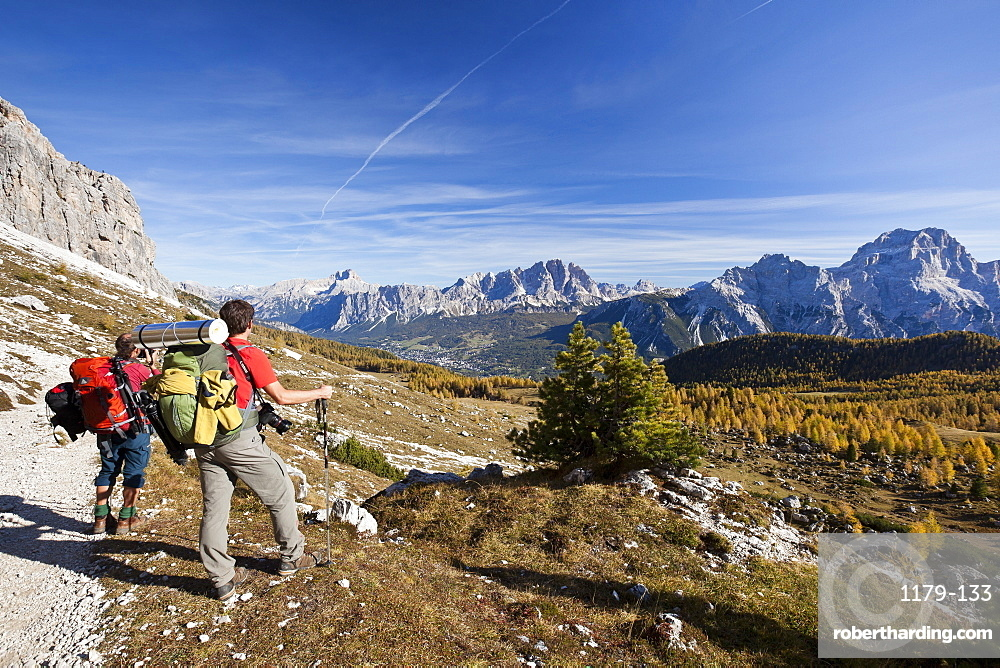 Hikers admiring the landscape of the Dolomites in its autumn colours, South Tyrol, Italy, Europe