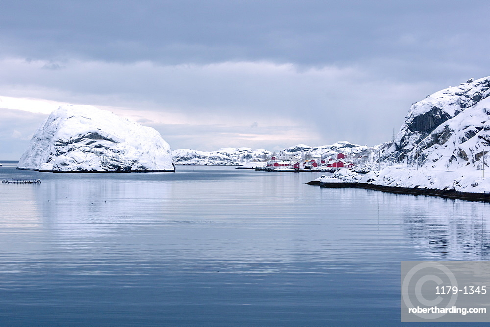 Cold sea and snowy peaks frame the fishing village at dusk, Nusfjord, Nordland, Lofoten Islands, Northern Norway, Scandinavia, Europe