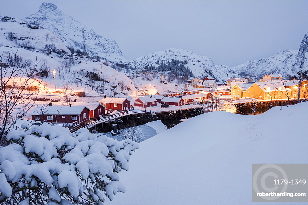 Dusk lights on the fishing village surrounded by snowy peaks, Nusfjord, Nordland, Lofoten Islands, Northern Norway, Scandinavia, Europe