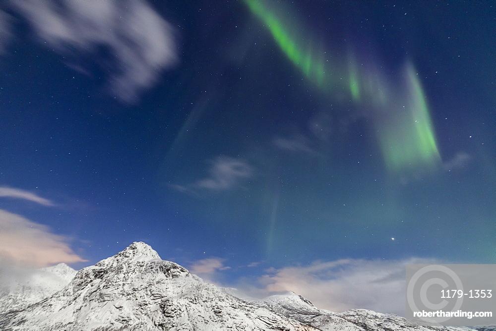 Northern lights (Aurora Borealis) and stars light up the snowy peaks, Vareid, Flakstad, Nordland, Lofoten Islands, Northern Norway, Scandinavia, Europe