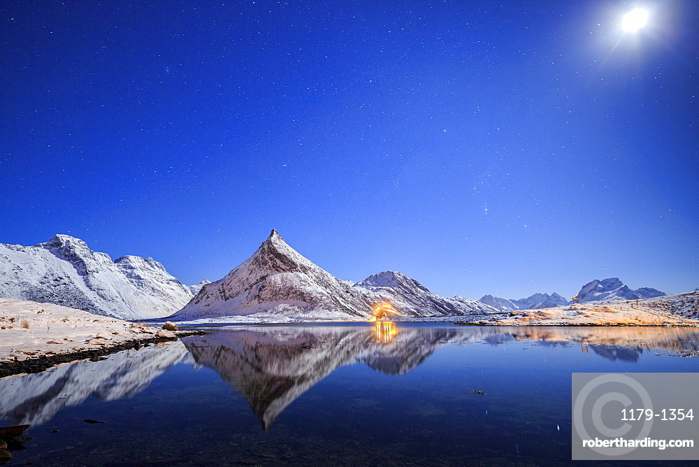 Full moon and stars light up the snow capped peaks reflected in sea, Volanstinden, Fredvang, Lofoten Islands, Northern Norway, Scandinavia, Europe