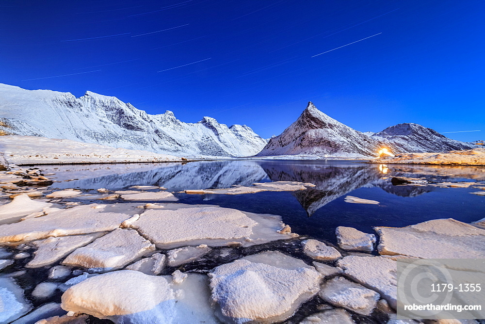 Star trails and lights on the snowy peaks reflected in the cold sea, Volanstinden, Fredvang, Lofoten Islands, Northern Norway, Scandinavia, Europe