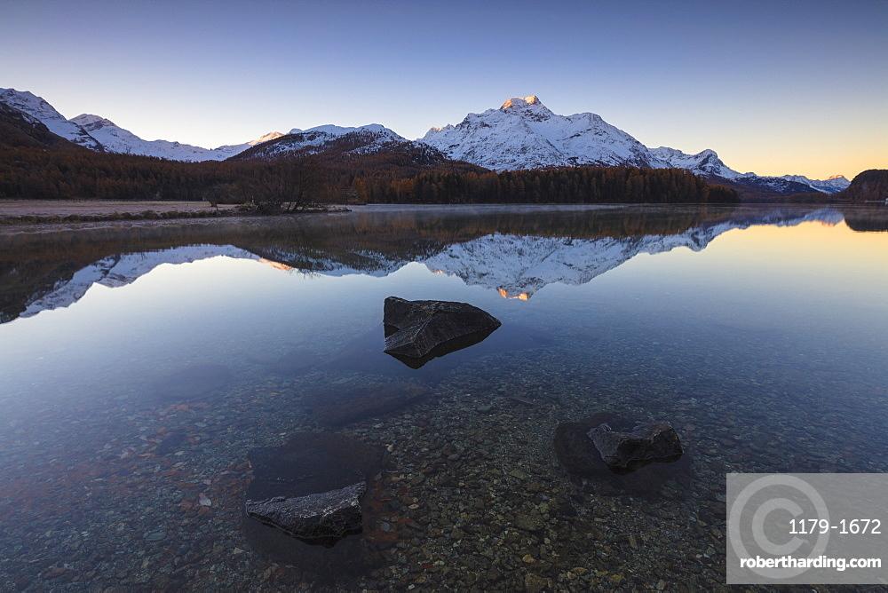 The snowy peaks are reflected in Lake Champfer at sunrise, St. Moritz, Canton of Graubunden, Engadine, Switzerland, Europe