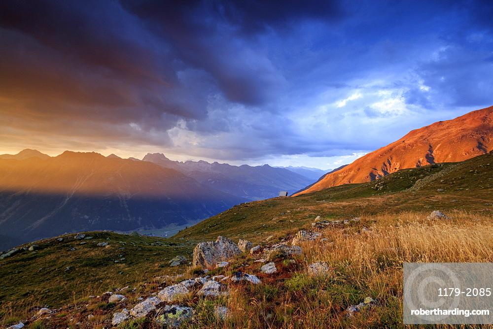 Fiery sky and dark clouds on high peaks of Muottas Muragl at sunset, St. Moritz, Canton of Graubunden, Engadine, Switzerland, Europe