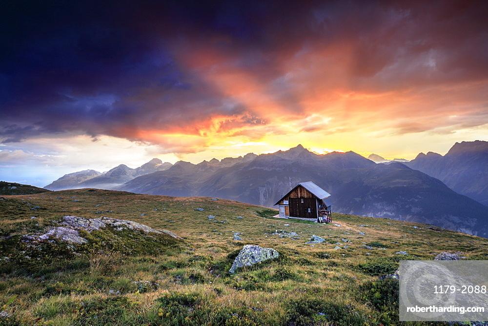 Wooden hut under fiery sky and clouds at sunset, Muottas Muragl, St. Moritz, Canton of Graubunden, Engadine, Switzerland, Europe