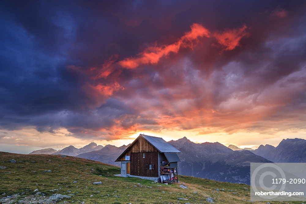 Wooden hut framed by fiery sky and clouds at sunset, Muottas Muragl, St. Moritz, Canton of Graubunden, Engadine, Switzerland, Europe