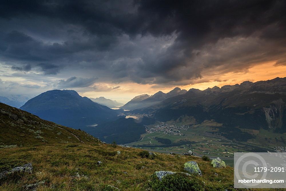 Dark clouds and sunset lights frame the rocky peaks of Muottas Muragl, St. Moritz, Canton of Graubunden, Engadine, Switzerland, Europe