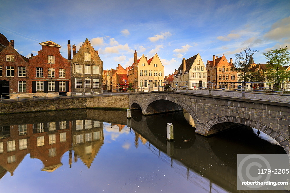 First light of sunrise on the historic buildings and bridge reflected in the typical canal, Bruges, West Flanders, Belgium, Europe