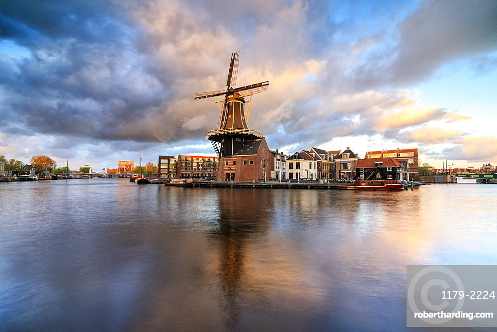 Pink clouds at sunset on the Windmill De Adriaan reflected in the River Spaarne, Haarlem, North Holland, The Netherlands, Europe