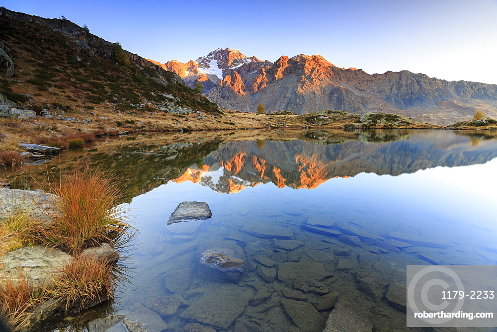 Rocky peaks of Mount Disgrazia reflected in Lake Zana at sunrise, Malenco Valley, Valtellina, Lombardy, Italy, Europe