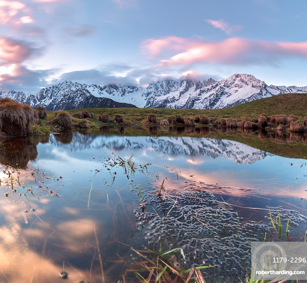 Panorama of pink clouds reflected in water at dawn, Tombal, Soglio, Bregaglia Valley, canton of Graubunden, Switzerland, Europe