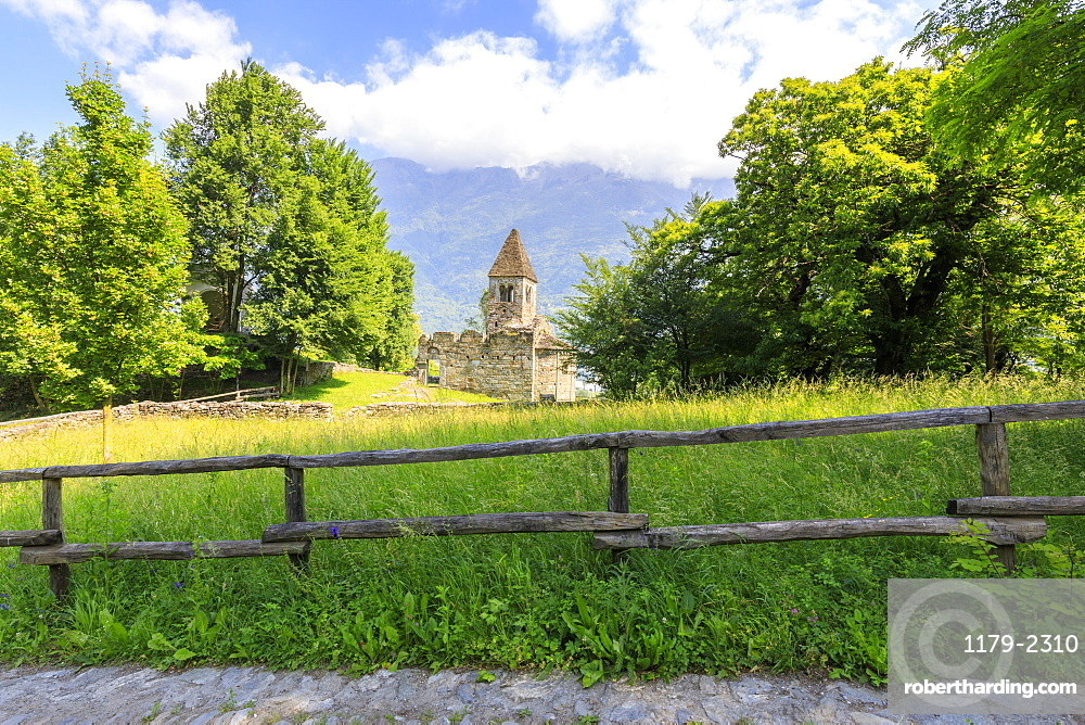 The medieval Abbey of San Pietro in Vallate framed by meadows, Piagno, Sondrio province, Lower Valtellina, Lombardy, Italy, Europe