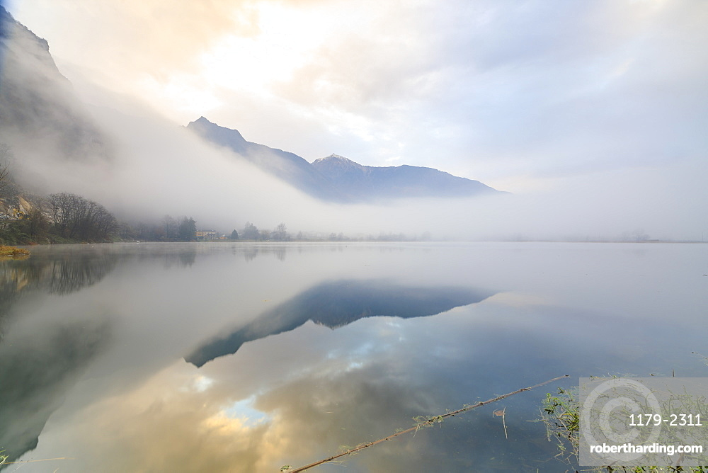 Mountains reflected in water at dawn shrouded by mist, Pozzo di Riva Novate, Mezzola, Chiavenna Valley, Lombardy, Italy, Europe