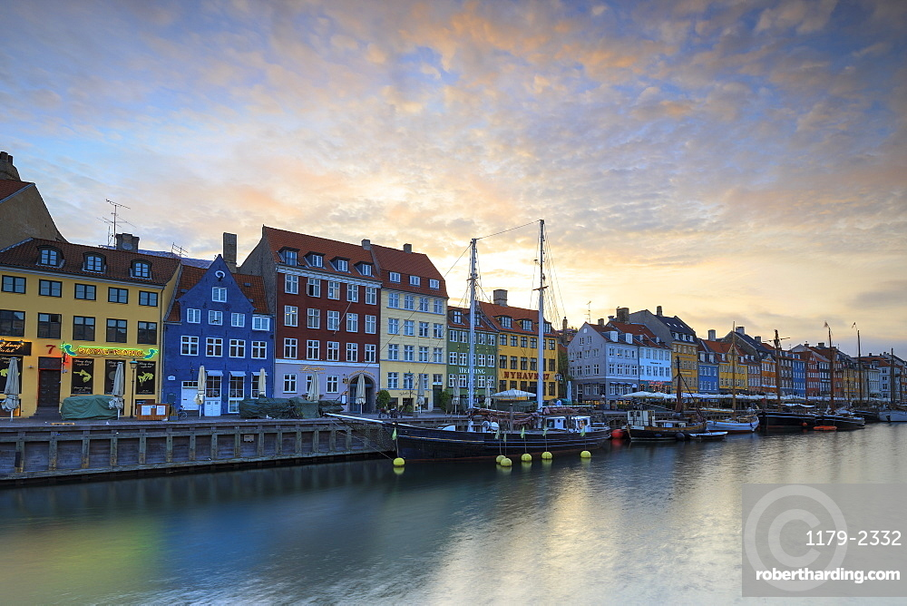 Sunrise on the colourful facades along the harbour in the district of Nyhavn, Copenhagen, Denmark, Europe