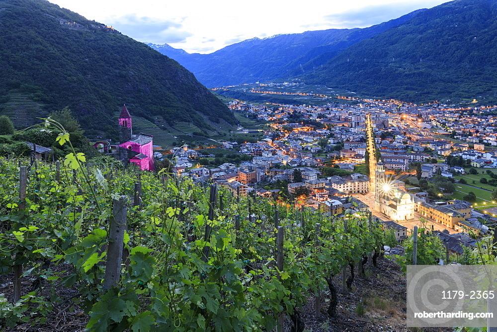 Ancient Xenodochio of Santa Perpetua and the illuminated town of Tirano, province of Sondrio, Valtellina, Lombardy, Italy, Europe