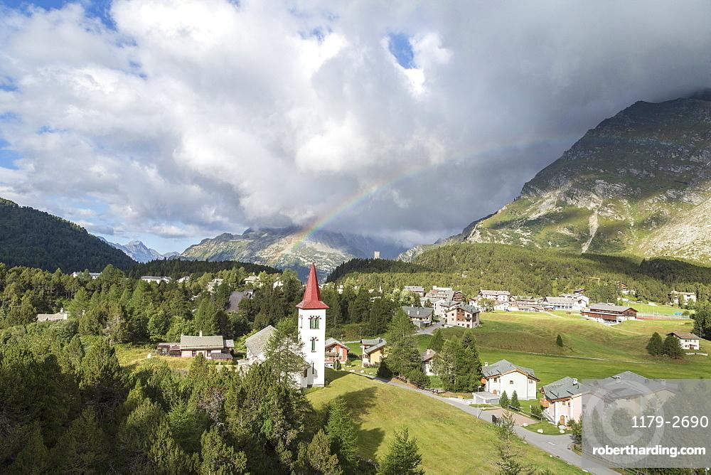 Rainbow over Chiesa Bianca and the village of Maloja, Bregaglia Valley, Engadine, Canton of Graubunden (Grisons), Switzerland, Europe